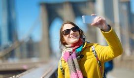 Turista felice della giovane donna che fa un giro turistico al ponte di Brooklyn, New York, al giorno di molla soleggiato Viaggia fotografie stock