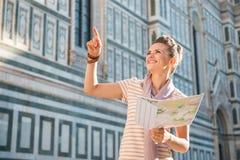 Turista feliz de la mujer con el mapa que señala en algo cerca de Duomo Imagen de archivo
