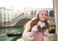 Turista feliz de la mujer con la cámara retra de la foto cerca del puente de Rialto Imagen de archivo
