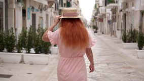 Turista feliz de la mujer joven que camina a través de las calles de una ciudad europea vieja y que sonríe mirando la cámara almacen de video