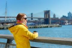 Turista feliz de la mujer joven que hace turismo en New York City en el día de primavera soleado Café de consumición del viajero  foto de archivo libre de regalías