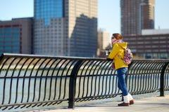 Turista feliz de la mujer joven que hace turismo en New York City en el día de primavera soleado Café de consumición del viajero  imagen de archivo