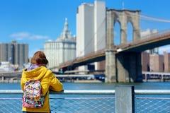 Turista feliz de la mujer joven que hace turismo por el puente de Brooklyn, New York City, en el día de primavera soleado Viajero foto de archivo