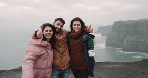 Turista feliz de tres amigos que presenta delante de la cámara para tomar imágenes de memorias en el lugar que sorprende de acant almacen de video