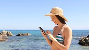 Turista feliz en contenido del teléfono de la ojeada del bikini de vacaciones