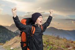 Turista feliz en el fondo de la puesta del sol de la montaña Imágenes de archivo libres de regalías