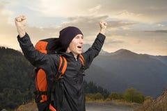 Turista feliz en el fondo de la puesta del sol de la montaña Foto de archivo libre de regalías