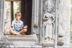Turista feliz joven de la muchacha del niño que medita en Angkor Wat, cambodi Fotografía de archivo libre de regalías