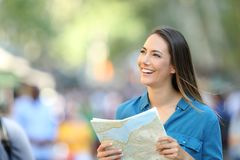 Turista feliz que hace turismo llevando a cabo una guía Foto de archivo libre de regalías