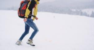 Turista feliz que joga com um cão branco grande no meio da montanha, viaja no whit do inverno sua laranja grande filme