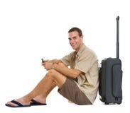 Turista feliz que se sienta cerca de bolso de las ruedas Fotos de archivo libres de regalías