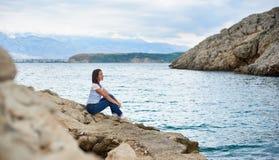 Turista femenino atractivo joven en vaqueros y camiseta que se sienta solamente en la orilla pedregosa del mar imagen de archivo