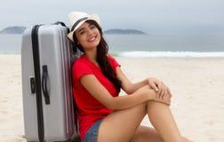 Turista femenino caucásico de risa con la maleta en la playa Fotografía de archivo