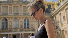Turista femenino caucásico hermoso que explora el mapa Muchos turistas multirraciales desconocidos borrosos en el cuadrado adentr almacen de metraje de vídeo