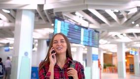 Turista femenino caucásico que usa smartphone en aeropuerto Ciérrese encima del tiro de la mujer joven que camina en el aeropuert metrajes