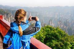 Turista femenino con el smartphone que toma la foto de montañas Fotos de archivo libres de regalías