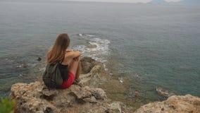 Turista femenino con la mochila que se sienta en una roca en fondo del cielo claro y del mar tranquilo almacen de metraje de vídeo