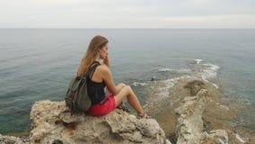 Turista femenino con la mochila que se sienta en una roca en fondo del cielo claro y del mar tranquilo almacen de video