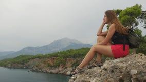Turista femenino con la mochila que se sienta en una roca en fondo del cielo claro y del mar tranquilo metrajes