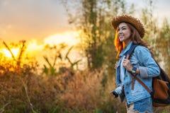 Turista femenino con la mochila y cámara en campo con puesta del sol foto de archivo