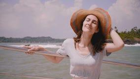 Turista femenino europeo hermoso joven feliz que presenta para la cámara en sorprender el barco exótico de la travesía del mar en metrajes
