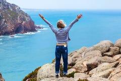 Turista femenino feliz que se coloca en el cabo Roca, Sintra, Portugal Imagen de archivo