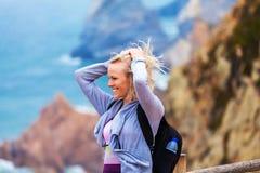 Turista femenino feliz que se coloca en el cabo Roca, Sintra, Portugal Fotografía de archivo