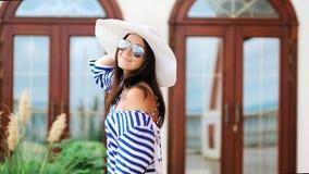 Turista femenino hermoso en las gafas de sol del sombrero y el vestido rayado que tienen la diversión y presentación metrajes