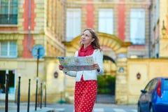 Turista femenino hermoso joven con el mapa en París Imágenes de archivo libres de regalías