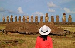Turista femenino impresionado por las ruinas de las estatuas de Moai en Ahu Tongariki en el sitio arqueológico de la isla de pasc imágenes de archivo libres de regalías