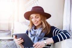 Turista femenino joven atractivo que charla con los colegas que hablan de su aventura en el extranjero mientras que se coloca en  Fotografía de archivo libre de regalías