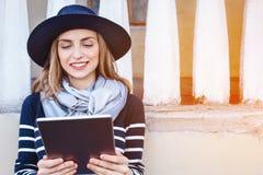 Turista femenino joven atractivo que charla con los colegas que hablan de su aventura en el extranjero mientras que se coloca en  Foto de archivo libre de regalías