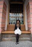 Turista femenino joven con la mirada de moda que descansa después de caminar en la ciudad durante su viaje asombroso Imagenes de archivo