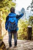 Turista femenino joven con la mochila azul que señala en las montañas Fotos de archivo libres de regalías