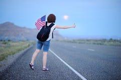 Turista femenino joven que hace autostop a lo largo de un camino solitario Fotografía de archivo