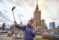 Turista femenino joven que hace la foto del selfie en el palacio hermoso del fondo de la cultura y de la ciencia en Varsovia Tene foto de archivo libre de regalías