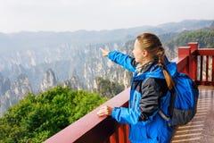Turista femenino joven que señala en las montañas hermosas Foto de archivo libre de regalías