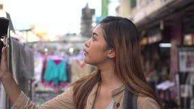 Turista femenino joven que sostiene un cardán con smartphone y que registra los vídeos Blogger y vlogger del viaje almacen de metraje de vídeo