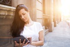Turista femenino magnífico que usa la almohadilla táctil para la navegación en ciudad durante vacaciones en el extranjero Imágenes de archivo libres de regalías