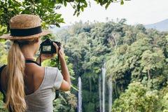 Turista femenino que fotografía una cascada en bosque Imágenes de archivo libres de regalías