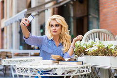 Turista femenino que presenta mientras que se fotografía para la imagen social de la red durante resto en cafetería al aire libre Fotos de archivo libres de regalías