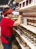 Turista femenino que prueba una inmersión de la muestra en la tienda foto de archivo