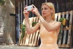 Turista femenino que toma la imagen con su teléfono elegante mientras que se sienta al aire libre en el día soleado hermoso Fotografía de archivo