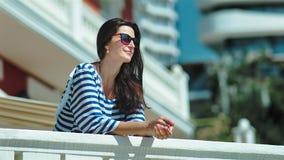 Turista femenino sonriente feliz en las gafas de sol y el vestido rayado que ponen las manos en la verja blanca almacen de video