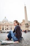Turista femminile abbastanza giovane che studia un programma Immagine Stock