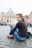 Turista femminile abbastanza giovane che studia un programma Immagine Stock Libera da Diritti