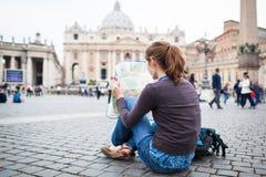 Turista femminile abbastanza giovane che studia un programma Immagini Stock