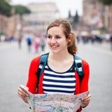 Turista femminile abbastanza giovane che tiene un programma Immagine Stock Libera da Diritti