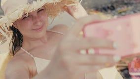 Turista femminile abbastanza giovane con il selfie di viaggio delle prese del cappello alla spiaggia mentre vacanze estive archivi video