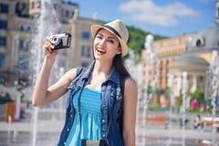 Turista femminile allegro che prende le foto della città Fotografia Stock